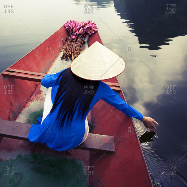 Vietnamese women wearing traditional costume, sitting on boat