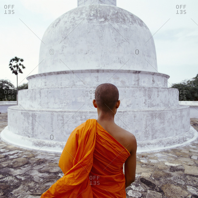 Buddhist monk standing in front of stupa