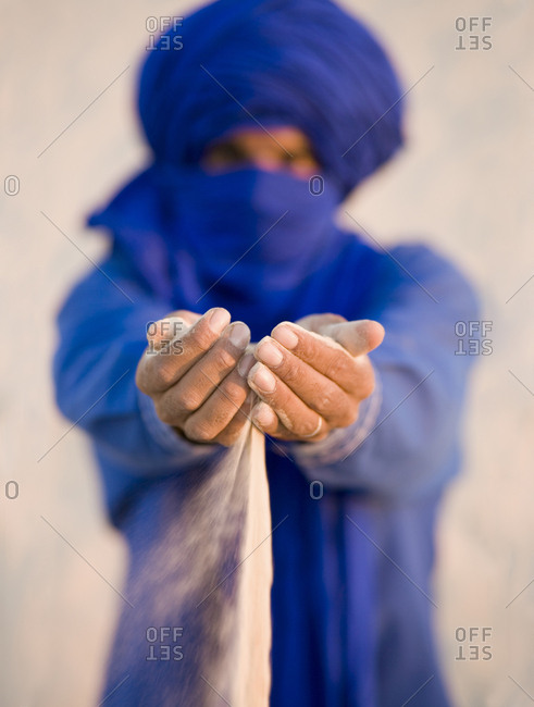 Tuareg tribesman sifting sand through his fingers in the Sahara desert