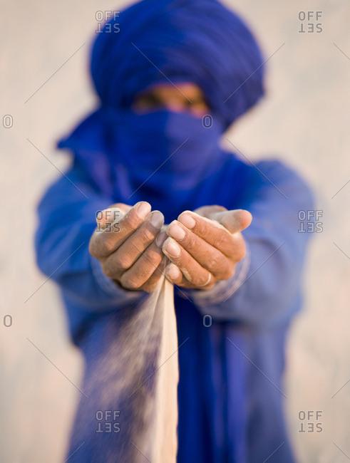 Tuareg tribesman sifting sand through his fingers in the Sahara desert