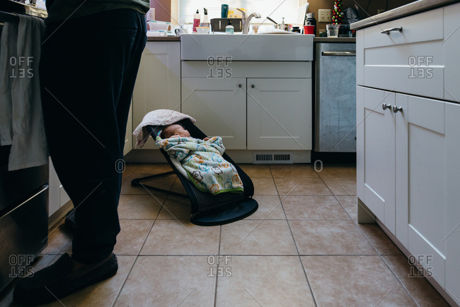 Baby sleeps in bouncer in kitchen