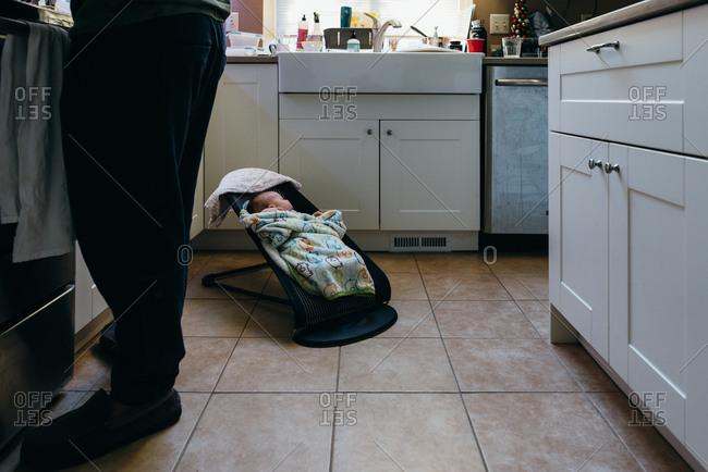 Baby sleeps in bouncer in kitchen