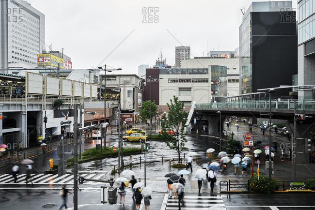 Tokyo, Japan - July 6, 2015: Local Japanese businesspeople rush through rain at Akihabara metro station toward end of work day