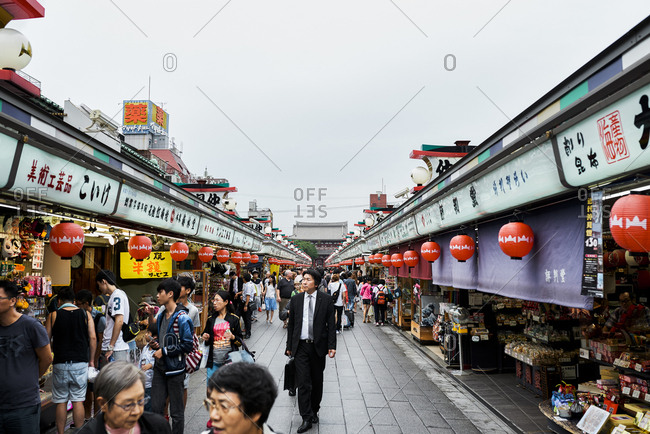 Tokyo, Japan - July 7, 2015: Man dressed in business suit wanders the main street in tourist-filled Asakusa entertainment district