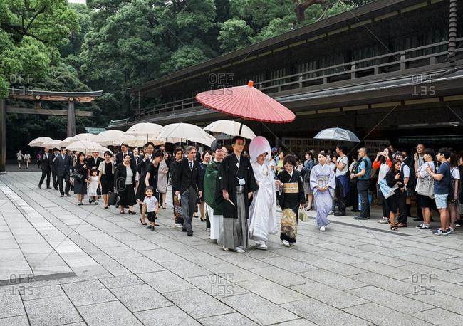 Tokyo, Japan - July 4, 2015: Bride in traditional white dress leading Japanese wedding ceremony procession in Meiji Shrine complex in Yoyogi Park near Shibuya