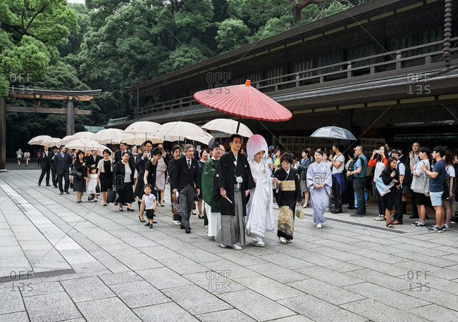 Tokyo, Japan - July 4, 2015: Bride in traditional white dress leading Japanese wedding ceremony procession in Meiji Shrine complex in Yoyogi Park near Shibuya