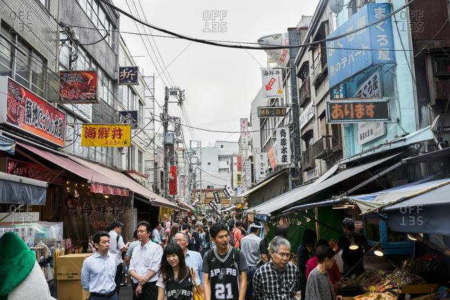 Tokyo, Japan - July 6, 2015: Young tourist couple wearing matching Spurs jerseys wander the streets of Tsukiji fish market