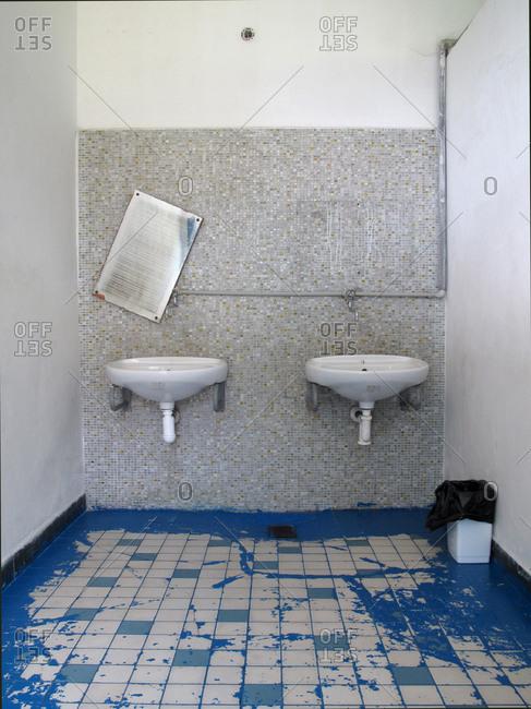 Sinks in public bathroom with mirror askew