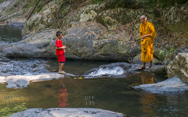 Pran Buri, Thailand - February 6, 2020: Monk helping a boy cross a rive