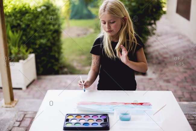 Young girl painting with watercolors on outdoor table