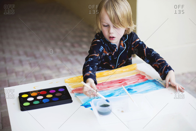 Boy in pajamas painting with watercolors