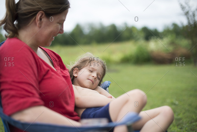 Girl lying in mom's lap in summer yard