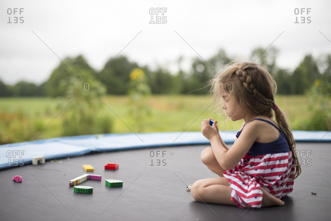 Girl playing with toys on trampoline