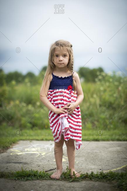 Girl in rural yard in striped dress