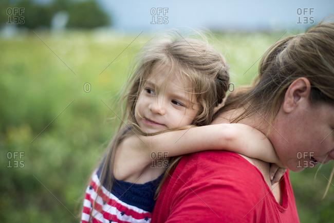Girl on mom's back in rural setting