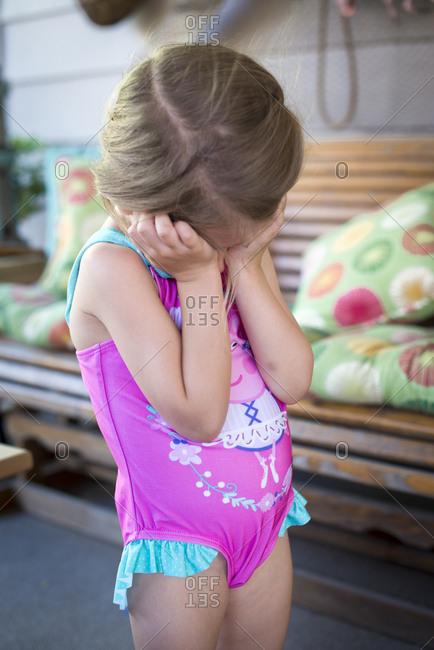 Girl in swimsuit hiding face