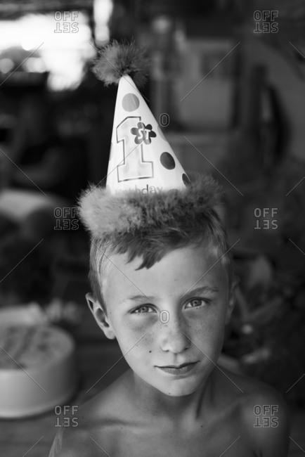 Boy wearing birthday hat in house