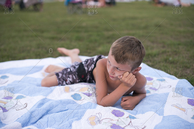 Boy lying on blanket in a field