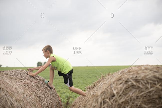 Boy climbing over hay bales
