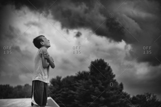 Boy watching storm clouds outside