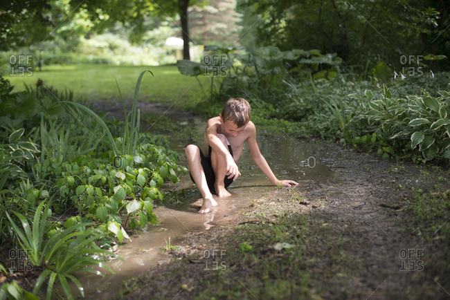 Boy sitting on muddy ground