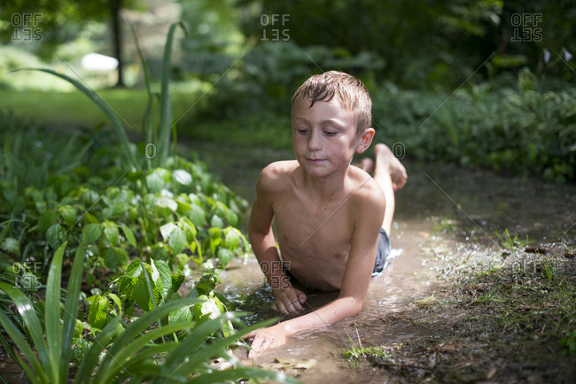 Boy laying in muddy ground