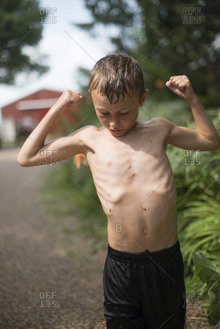 Boy flexing arms in yard
