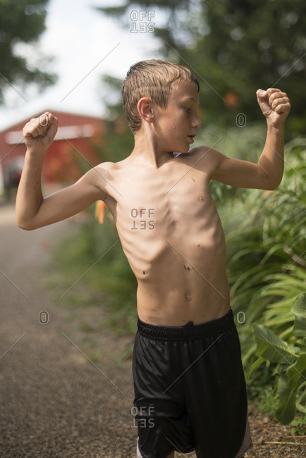 Boy flexing his arms in yard