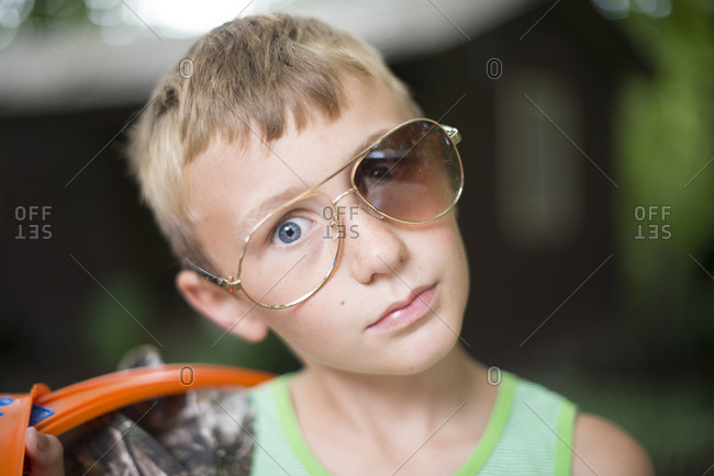 Boy making face in broken sunglasses