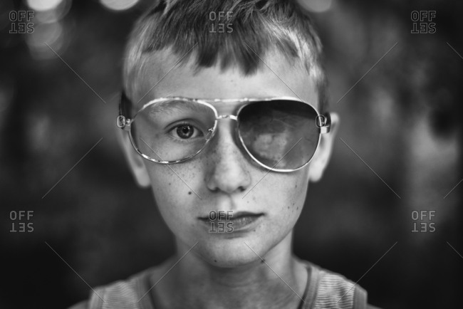 Boy in sunglasses with missing lens