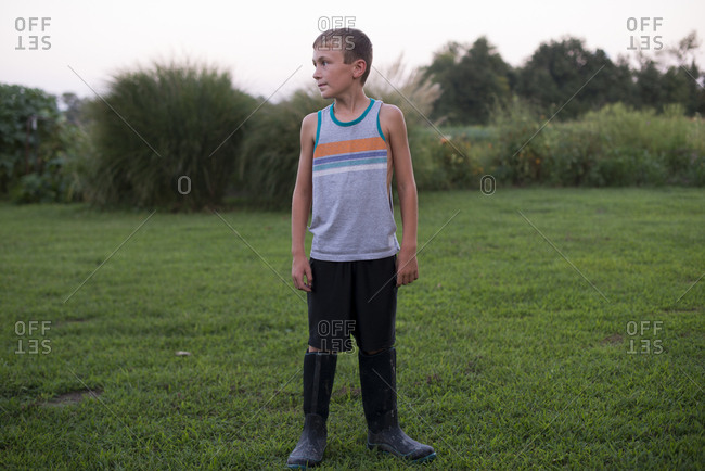 Boy in rubber boots outside