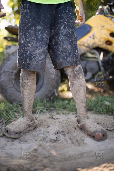 Boy in mud by four wheeler