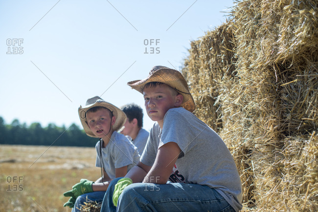 Boys on hay bales during field work