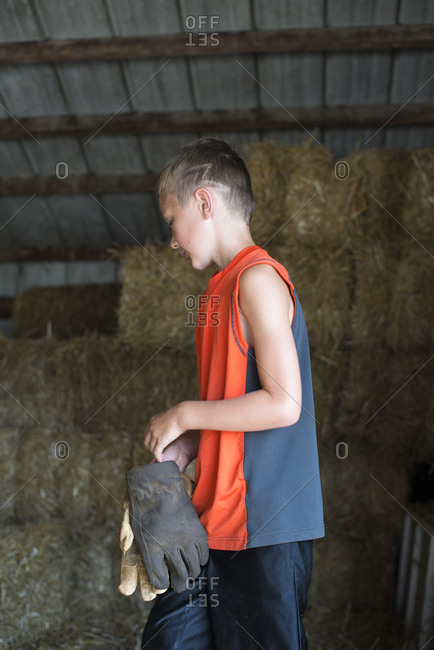 Boy in a barn with gloves