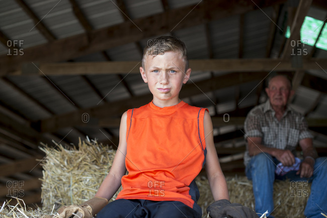 Man and boy on hay in shed
