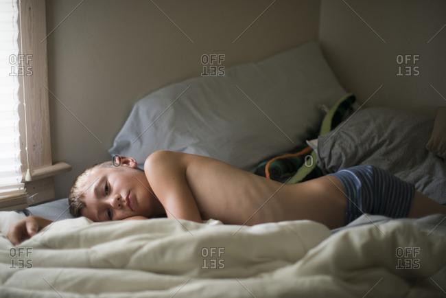 Boy lying across a bed
