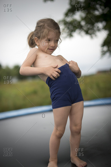 Girl standing in shorts on trampoline