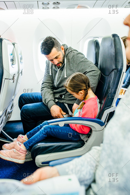 Man buckles his daughter in airplane seat
