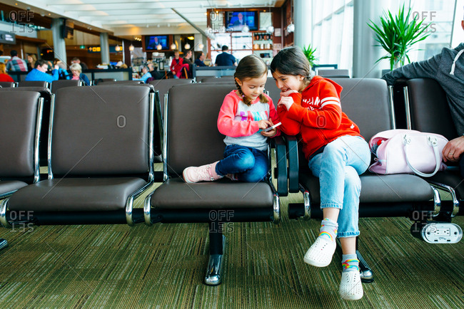 Two sisters playing with phone in airport waiting area