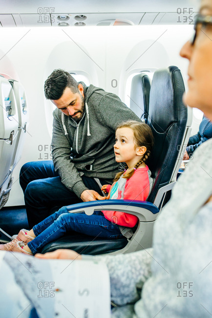 Man helping his daughter with seatbelt in airplane