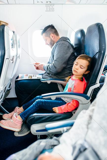 Girl sleeping on airplane while father uses smartphone