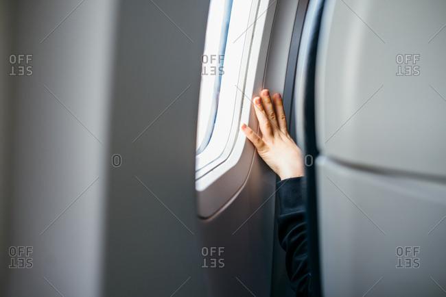 Child's hand on airplane window