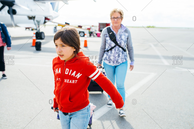 Girl with grandmother and luggage on airport tarmac