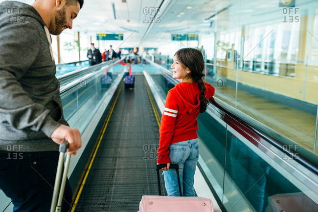 Girl on moving walkway in airport with father