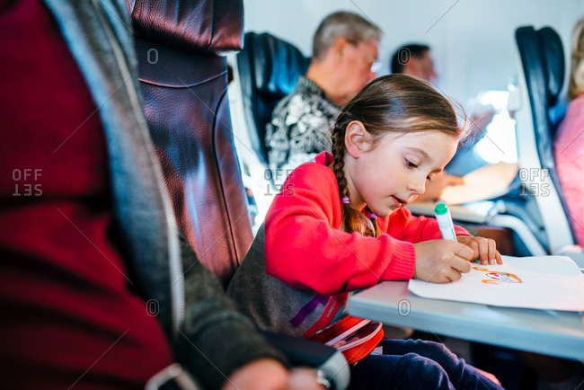 Girl drawing with markers on flight