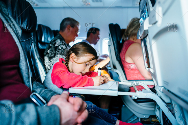 Girl coloring with markers on airplane