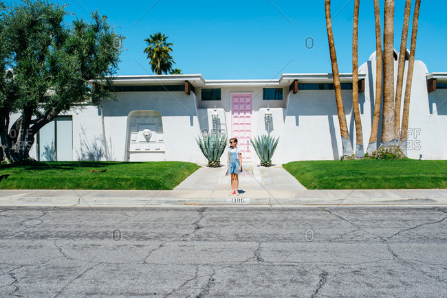 Girl standing on sidewalk in front of mid-century modern house