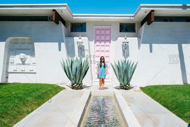 Girl standing at front door of house with fountain