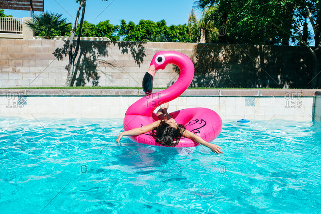 Girl lounging on flamingo float in pool