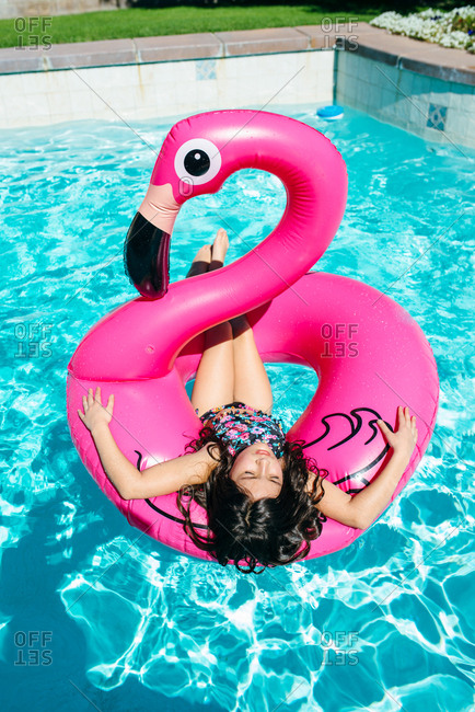 Girl lying on flamingo float in pool